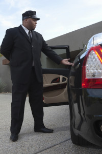 Mixed race chauffeur helps woman to get down from luxury car